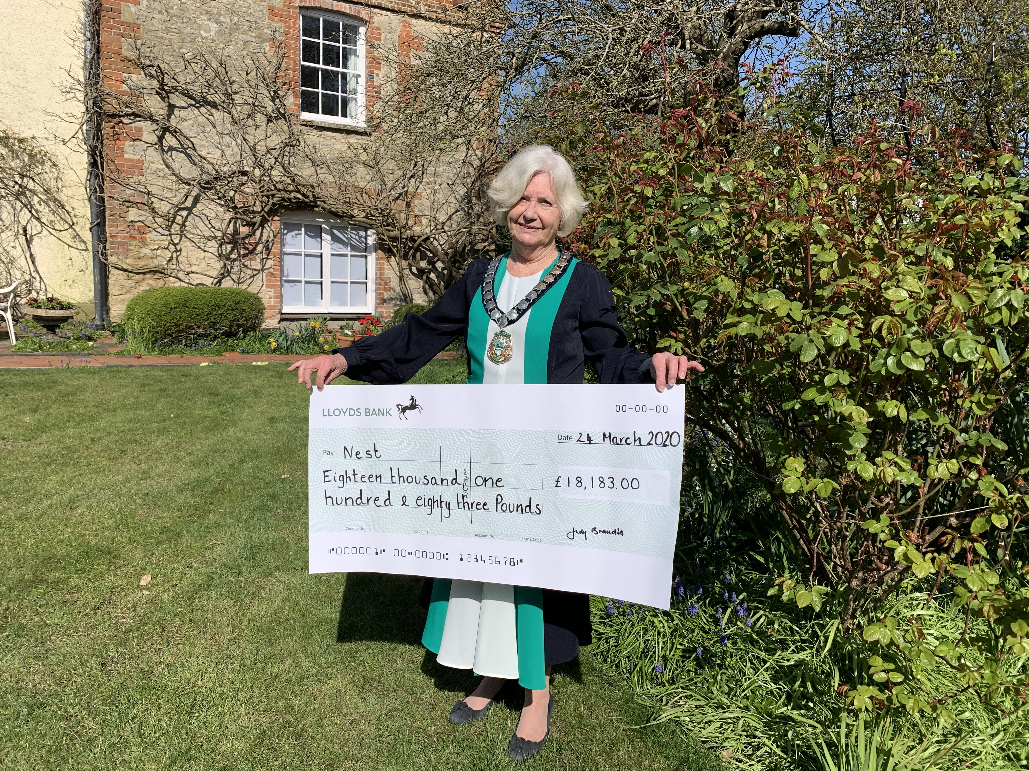 Cllr Judy Brandis in her her garden with the presentation cheque for Nest Aylesbury Vale for £18,183